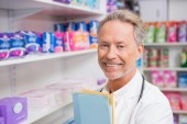 Senior pharmacist holding documents — Stock Photo