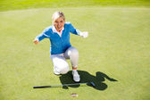 Excited lady golfer cheering on putting green  — Stock Photo