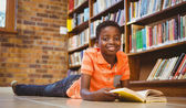 Cute boy reading book in library — Stock fotografie