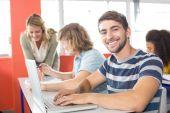 Gülümseyen erkek öğrenci sınıfta dizüstü bilgisayar kullanmak — Stok fotoğraf