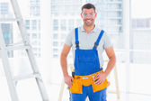 Smiling repairman in overalls at bright office — Stockfoto