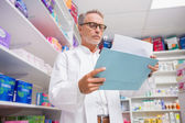 Concentrated pharmacist reading documents — Stock Photo