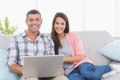 Happy couple with laptop on sofa — Stock Photo