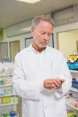 Concentrated pharmacist looking at medicine — Stock Photo