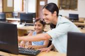 Cute pupil in computer class with teacher — Stock Photo