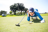 Female golfer blowing her ball on putting green — Stock Photo