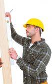 Carpenter using spirit level on wood plank — Stock Photo