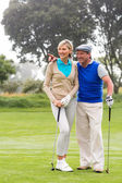 Golfing couple walking on putting green — Stock Photo