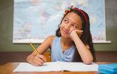 Girl writing book in classroom — Stock Photo