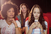 Annoying woman texting during movie — Stock Photo