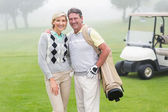 Golfing couple with golf buggy behind — Stock Photo