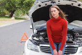Annoyed young woman beside her broken down car — Stock Photo