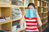 Student covering face with book in library — Stock Photo