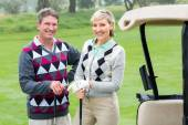 Golfing couple with golf buggy beside — Stock Photo