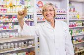 Smiling pharmacist showing medication at camera — ストック写真