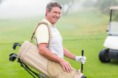 Happy golfer with golf buggy behind — Stockfoto