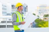 Architect in protective workwear holding blueprints — Stock Photo