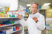 Concentrated pharmacist reading prescription — Stock Photo