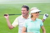 Golfing couple smiling and holding clubs — Stock Photo