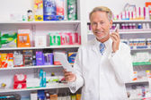 Smiling senior phoning while reading prescription — Stock Photo