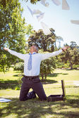 Businessman tossing papers in the park — Stock Photo