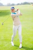Female golfer taking a shot and smiling — Stock Photo