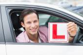 Driver smiling and holding l plate — Stock Photo