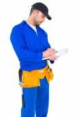 Handyman writing on clipboard — Stock Photo