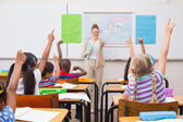 Pupils raising hand during geography lesson in classroom — Stock Photo