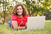 Handsome hipster using laptop in the park — Foto Stock