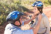 Father clipping on sons helmet — Stock Photo