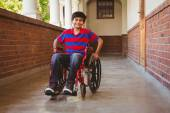 Boy sitting in wheelchair in school corridor — Stock Photo
