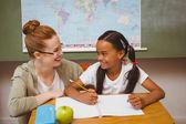 Leraar bijstaan meisje met huiswerk in klas — Stockfoto