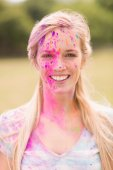 Happy blonde covered in powder paint — Stockfoto