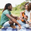 Young couple on picnic playing guitar — Stock Photo #69002309