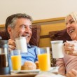 Happy mature couple having breakfast in bed — Stock Photo #69002765