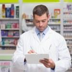 Pharmacist writing on clipboard — Stock Photo #69002791