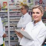 Pharmacist writing on clipboard — Stock Photo #69003355