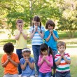 Children saying their prayers in park — Stock Photo #69004295