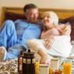 Happy mature couple having breakfast in bed — Stock Photo #69004331