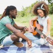 Couple on a picnic playing guitar — Stock Photo #69004337