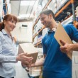 Delivery man passing parcel to warehouse manager — Stock Photo #69004625