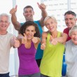 Friends gesturing thumbs up in fitness club — Stock Photo #69004631