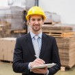 Warehouse manager writing on clipboard — Stock Photo #69004671