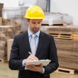 Warehouse manager writing on clipboard — Stock Photo #69005125