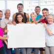 Happy people holding blank billboard at health club — Stock Photo #69006095