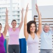 Female friends with arms raised exercising in gym — Stock Photo #69006421