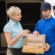Delivery driver showing where to sign — Stock Photo #69007079
