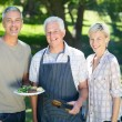 Couple with grandfather doing barbecue — Stock Photo #69007191