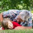 Father playing on grass with his son — Stock Photo #69008755